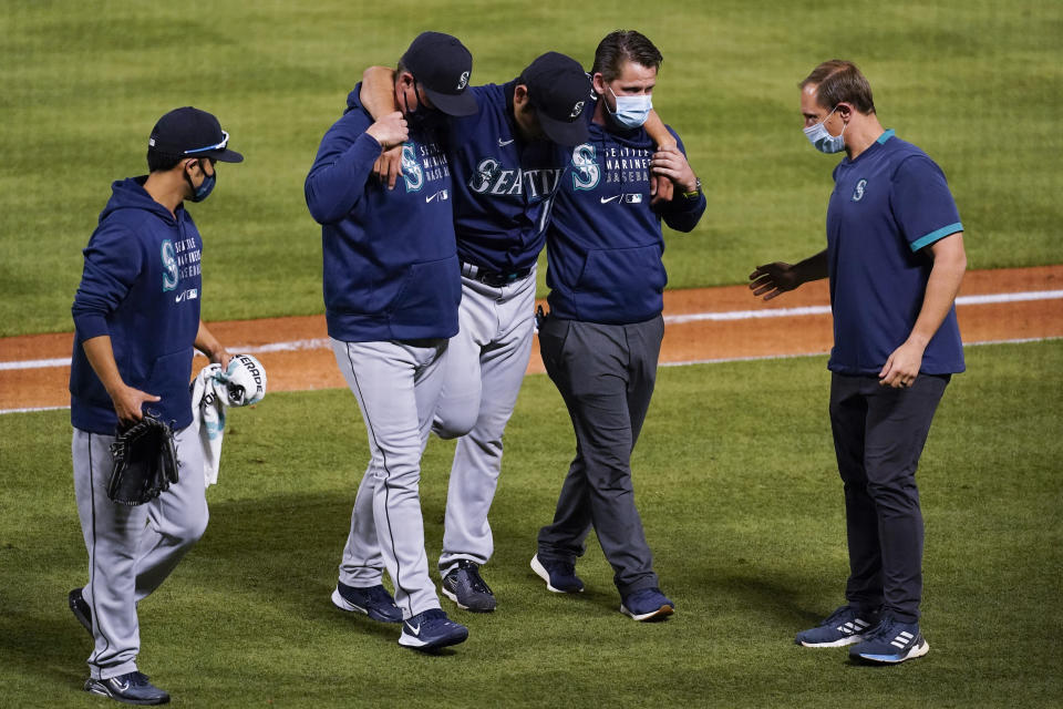 Seattle Mariners starting pitcher Yusei Kikuchi, center, is helped off the field after being hit by a ball hit by Los Angeles Angels' David Fletcher during the fifth inning of a baseball game Saturday, June 5, 2021, in Anaheim, Calif. (AP Photo/Ashley Landis)