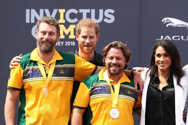 Harry and Meghan pose with Silver medallists Craig McGrath and Scott Reynolds of Australia during the medal ceremony during the JLR Drive Day at Cockatoo Island on Saturday.
