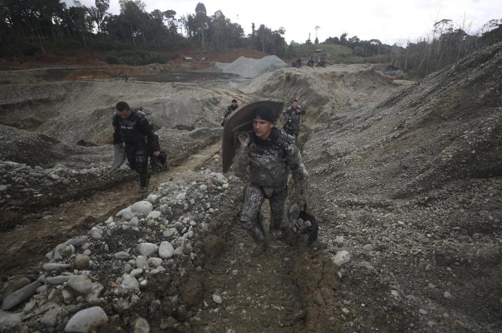 """National Police officers walk at an illegal gold mining operation as they work to destroy it as part of the Armed Forces' """"Operation Guamuez III"""" in Magui Payan, Colombia, Tuesday, April 20, 2021. Illegal gold mining is common in Colombia, especially wildcat mines in poverty-stricken areas dominated by criminal gangs with little state presence. (AP Photo/Fernando Vergara)"""