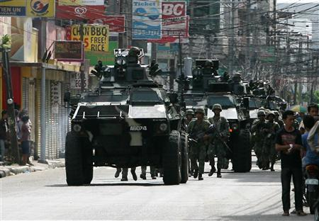 Government soldiers with armored personnel carriers move to reinforce the government forces battling the Moro National Liberation Front (MNLF) rebels near the hostile ground in Zamboanga City, southern Philippines