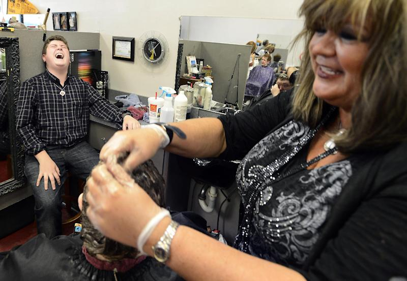 In this Oct. 10, 2013 photo, Tyler Edwards, left, jokes with his mother, Tammy Edwards, right, while she works at a hair salon in Hendersonville, Tenn. Tyler has several food allergies that include peanuts, coconut and beef. He carries epinephrine with him in an auto-injector in case of a reaction. (AP Photo/Mark Zaleski)