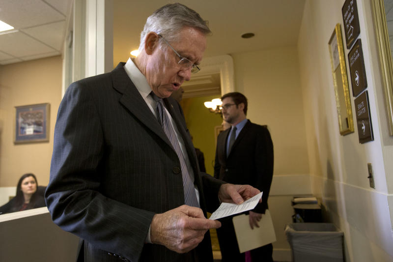 Senate Majority Leader Sen. Harry Reid, D-Nev., left, looks over his remarks before entering a news conference to speak about the fiscal cliff at the U.S. Capitol in Washington, on Thursday, Dec. 20, 2012. (AP Photo/Jacquelyn Martin)