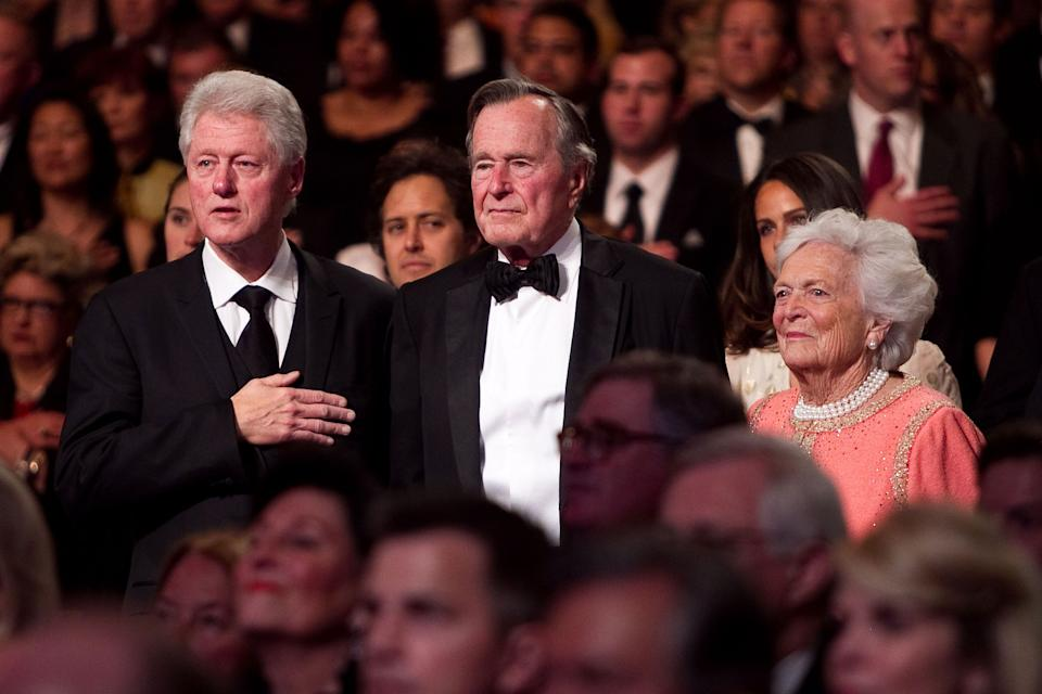 Former President Bill Clinton (left), former President George H.W. Bush and Barbara Bush stand for the National Anthem at the Points of Light Institute Tribute to George H.W. Bush at the John F. Kennedy Center for Performing Arts on March 21, 2011, in Washington, D.C.