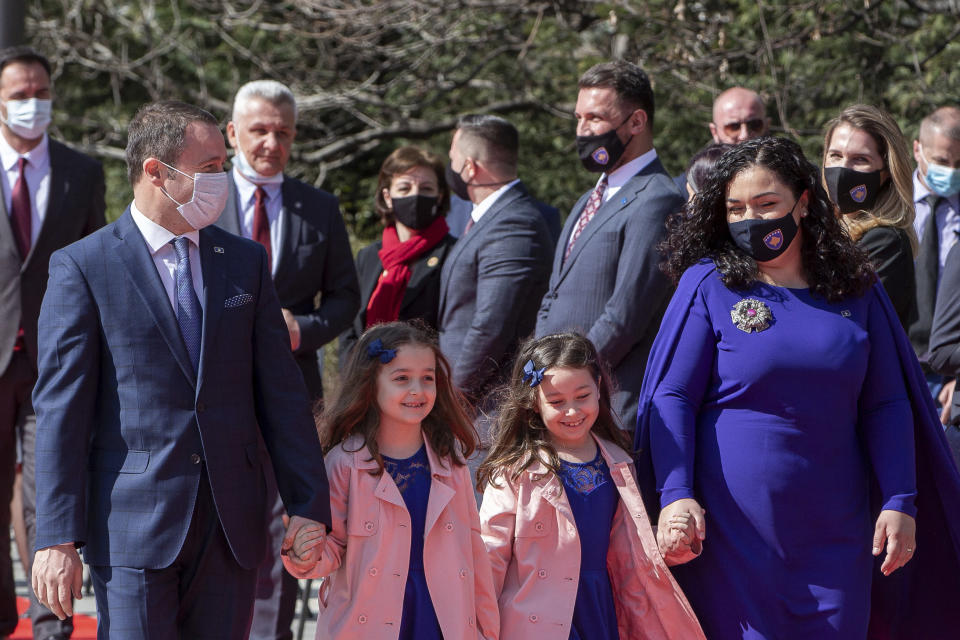 Kosovo newly elected president Vjosa Osmani Sadriu, with her husband Prindon Sadriu and their twin daughters Dua and Anda (left-right unknown), as they attend the presidential hand over ceremony in Pristina, Kosovo, on Tuesday, April 6, 2021. Osmani took over the presidency after being elected to the post during a two-day extraordinary session of parliament. (AP Photo/ Visar Kryeziu)