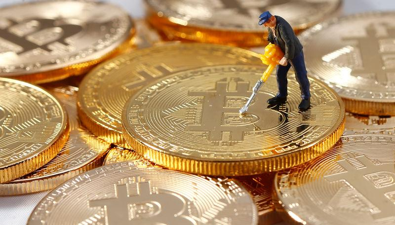A Small Toy Figure Is Seen On Representations Of The Bitcoin Virtual Currency In This Ilration