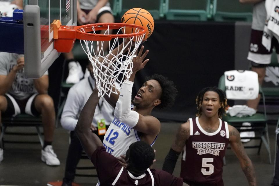 Memphis forward DeAndre Williams, center, takes a shot over Mississippi State forward Abdul Ado, left, in the first half of an NCAA college basketball championship game in the NIT, Sunday, March 28, 2021, in Frisco, Texas. (AP Photo/Tony Gutierrez)