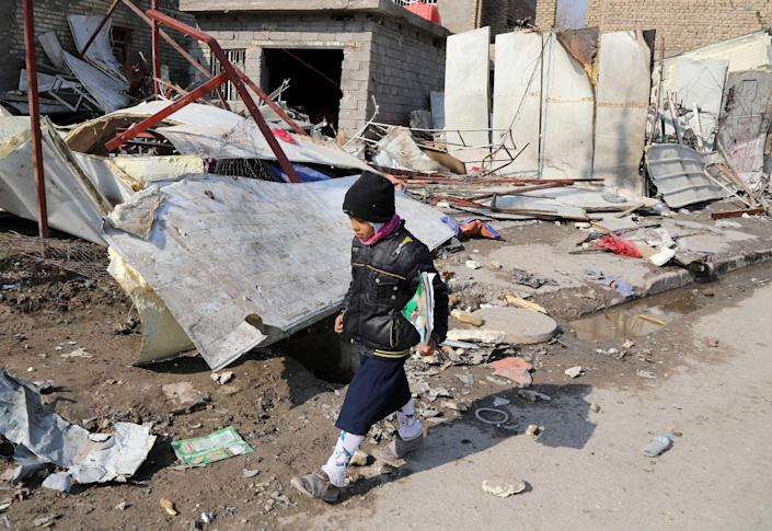 A school girl walks past rubble the day after a bombing in the Abu Disher neighborhood of southern Baghdad, Iraq, Tuesday, Jan. 21, 2014. Violence spiked in Iraq after the government staged a deadly crackdown on a Sunni protest camp last April. Militants have also targeted civilians, particularly in Shiite areas of Baghdad, with coordinated car bombings and other deadly attacks. (AP Photo/Karim Kadim)