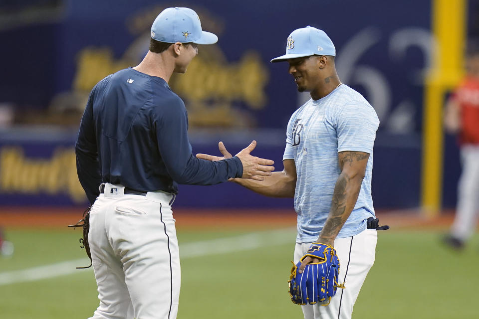 Tampa Bay Rays third baseman Wander Franco, right, shakes hands with fellow third baseman Joey Wendle before a baseball game against the Boston Red Sox Tuesday, June 22, 2021, in St. Petersburg, Fla. The Rays called Franco up from their Class AAA Durham team. (AP Photo/Chris O'Meara)