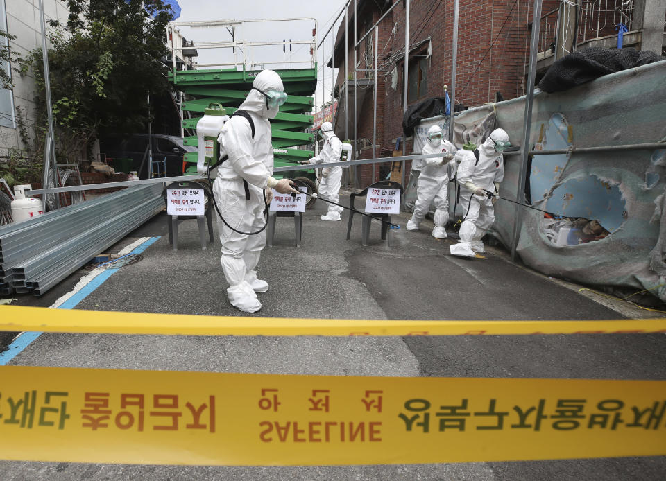 Public officials disinfect a church as a precaution against the coronavirus in Seoul, South Korea, Friday, Aug. 14, 2020. South Korea reported over 100 new virus cases Friday, one of its biggest daily jumps in months, as officials express concerned that infections are getting out of control in cities as people increasingly venture out in public. (Han Jong-chan/Yonhap via AP)