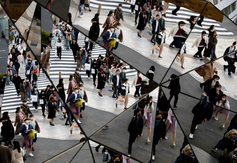 FILE PHOTO: Passersby wearing protective face masks, following an outbreak of the coronavirus disease (COVID-19), are reflected in mirrors at a shopping center in Tokyo