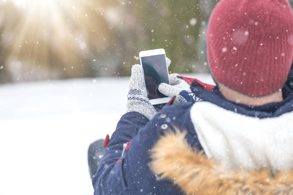 Rear view of man sitting in snow and holding blank screen smart phone.