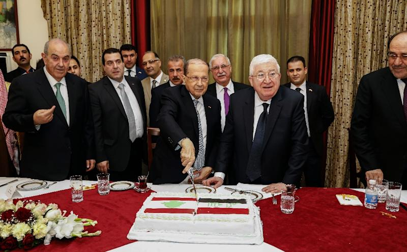 A handout picture from Lebanon's Dalati and Nohra photo agency shows Lebanese President Michel Aoun (C-L) cutting a cake presented to him by his Iraqi counterpart Fuad Masum (C-R) on February 20, 2018 during the first visit to Iraq by a Lebanese president