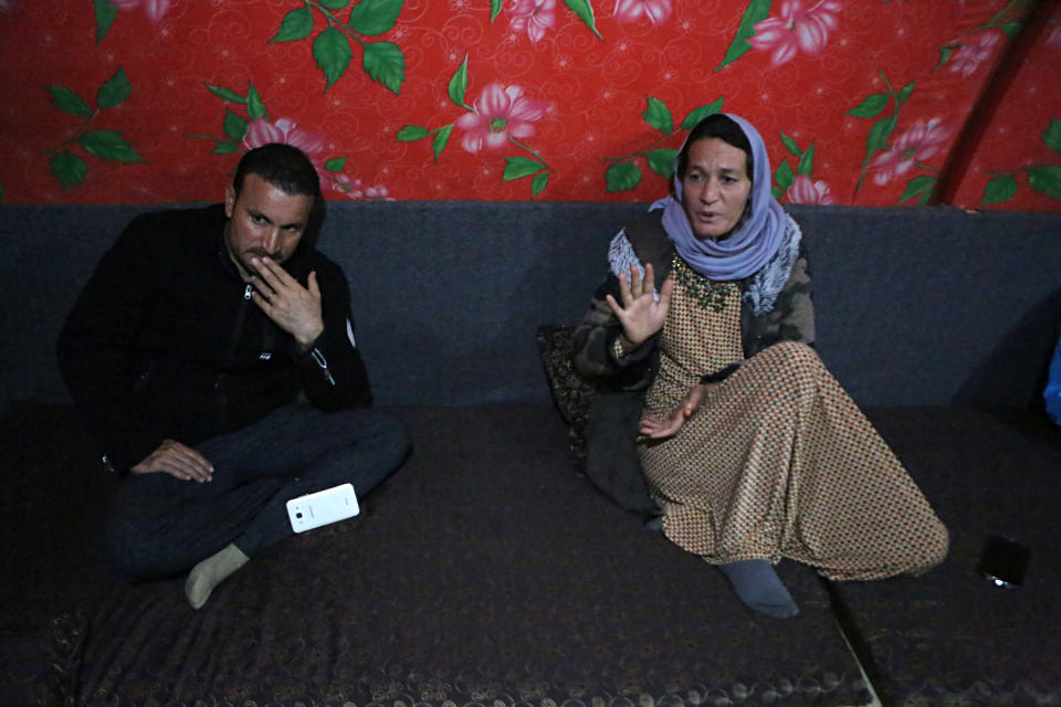 In this Thursday, Feb. 28, 2019 picture, Baseh Hammo, a Yazidi woman who escaped enslavement by Islamic State group militants, sits with a relative in a camp for displaced people outside Dahuk, Iraq. Yazidi women enslaved by IS who escaped captivity say there could be hundreds of other women still missing, women who may never return home. They say they fear many perished in bondage or war while others chose to remain in captivity to stay with the children they were forced to have. (AP Photo/Khalid Mohammed)