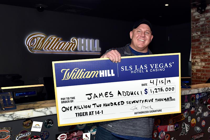 LAS VEGAS, NEVADA - APRIL 15: James Adducci of Wisconsin stands with a ceremonial check of his winnings after cashing his ticket at the William Hill Sports Book at SLS Las Vegas Hotel on April 15, 2019 in Las Vegas, Nevada. Adducci placed an USD 85,000 wager on golfer Tiger Woods to win the 2019 Masters Tournament. (Photo by David Becker/Getty Images for William Hill US)