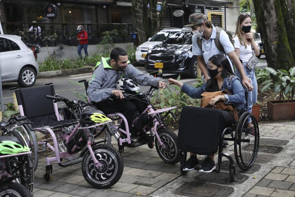 Martin Londoño, left, owner of MATT, an electric wheelchair tour company, greets a client in Medellin, Colombia, Wednesday, Nov. 18, 2020. Londoño, an entrepreneur who lost the use of his legs in a traffic accident is organizing electric wheelchair tours for people with disabilities or fully abled folks, in a bid to generate employment for people while creating awareness of the challenges faced by those on wheelchairs. (AP Photo/Fernando Vergara)
