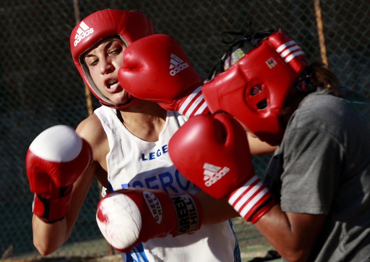 Italian boxer Romina Marenda (L) punches during a training session at the Military Olympic Center in Rome October 6, 2011. Lightweight Marenda will be one of Italy's biggest hopes when women's boxing makes its debut at the London Olympics this year, as long as she manages to qualify at the world championships in China in May. Picture taken October 6, 2011. REUTERS/Tony Gentile