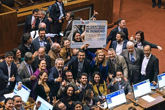 """Chilean deputies for the Frente Amplio party, celebrating in September with a giant fake Chilean Identity card reading """"My identity, my right"""", after voting a gender identity law that allows the change of name and sex in public records from the age of 14: it was signed into law Wednesday by President Sebastian Pinera (AFP Photo/FRANCESCO DEGASPERI)"""