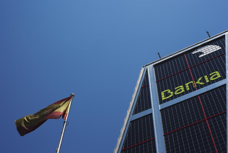 A Spanish flag flies next to the headquarters of Bankia bank in Madrid