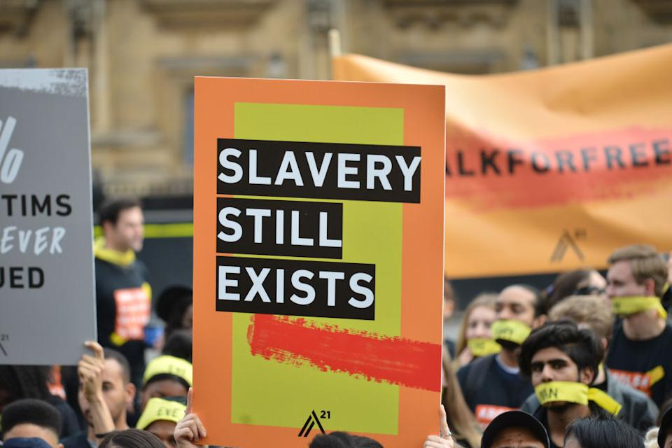 People marching against modern slavery through London wearing face masks representing the silence of modern slaves in forced labour and sexual exploitation on October 14, 2017 in London, England. | Barcroft Media via Getty Images—Mathew Chattle / Barcroft Media
