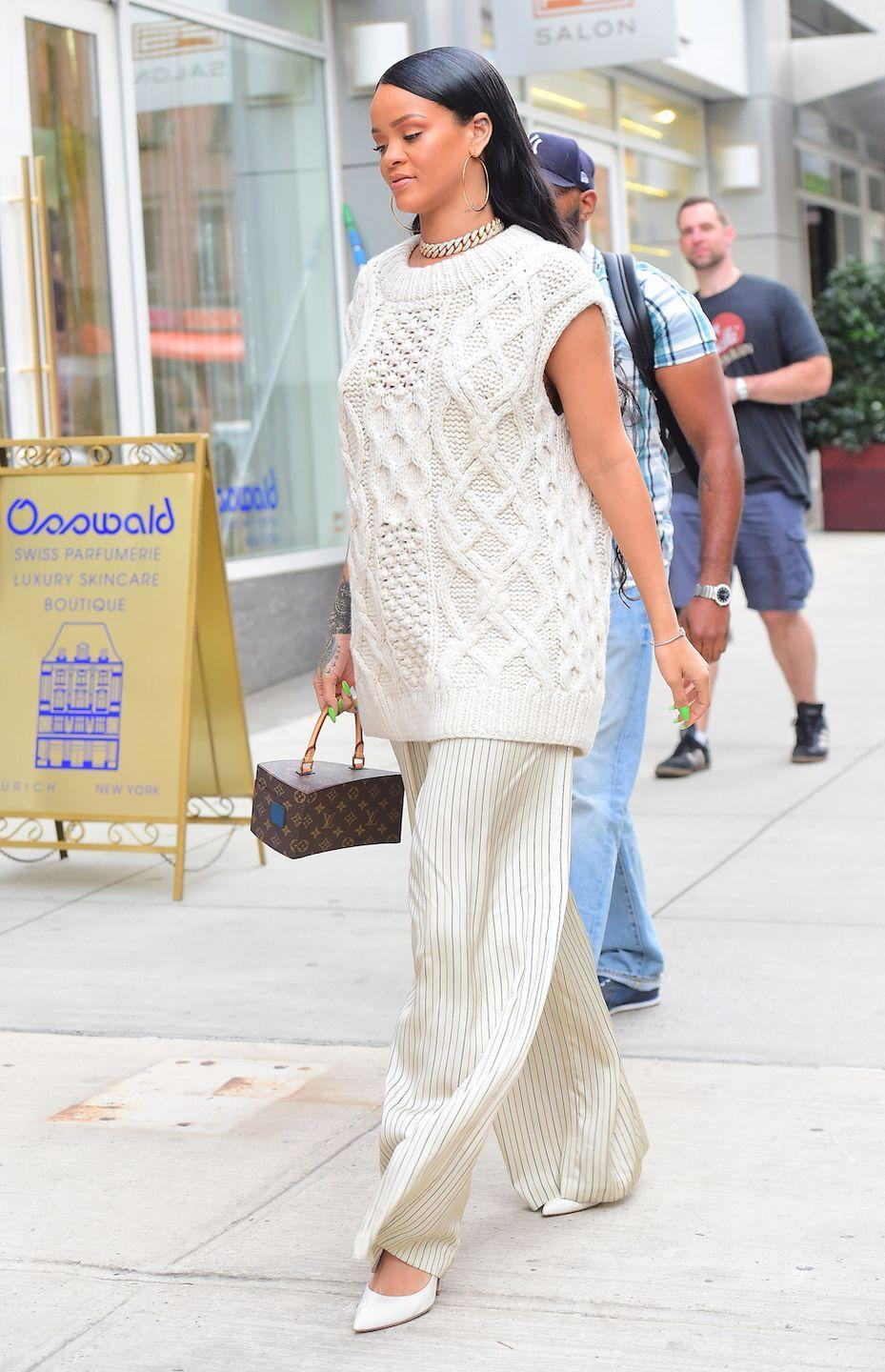 <p>Rihanna wears a cream sleeveless sweater, wide leg pin-striped pants, pointed-toe heels and a box bag by Louis Vuitton while out in NYC.</p>