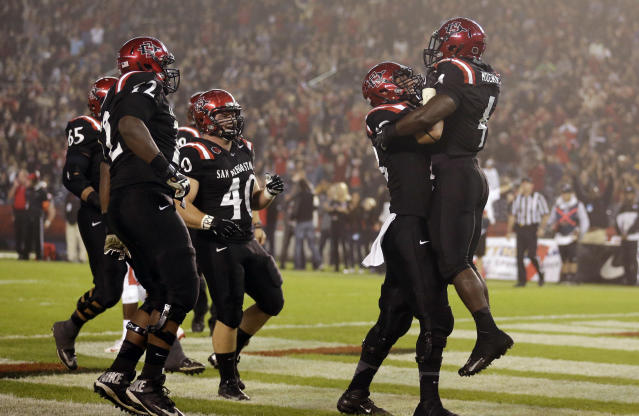 San Diego State running back Adam Muema, right, is lifted by teammate offensive linesman Bryce Quigley, second from right, after scoring a touchdown against Fresno State during the first half in an NCAA college football game Saturday, Oct. 26, 2013, in San Diego. (AP Photo/Gregory Bull)