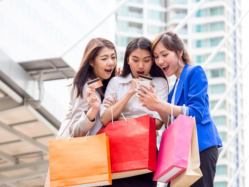 Three women with shopping bags looking at a smart phone together