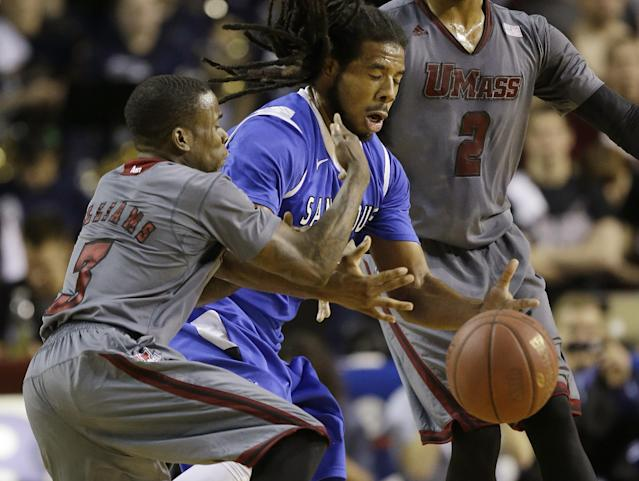 Saint Louis guard Jordair Jett, center, cannot get a handle on the ball after Massachusetts guard Chaz Williams (3) lost control during the first half of an NCAA college basketball game in Amherst, Mass., Sunday, March 9, 2014. (AP Photo/Stephan Savoia)