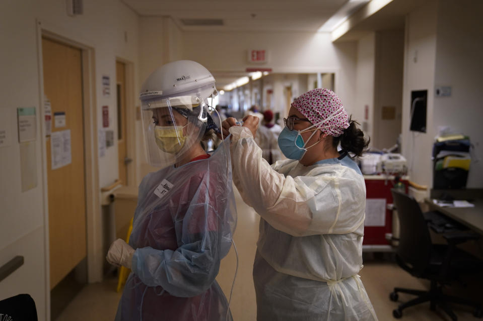 Registered nurse Dania Lima, right, helps fellow nurse Adriana Volynsky put on her personal protective equipment in a COVID-19 unit at Providence Holy Cross Medical Center in the Mission Hills section of Los Angeles, Tuesday, Dec. 22, 2020. (AP Photo/Jae C. Hong)