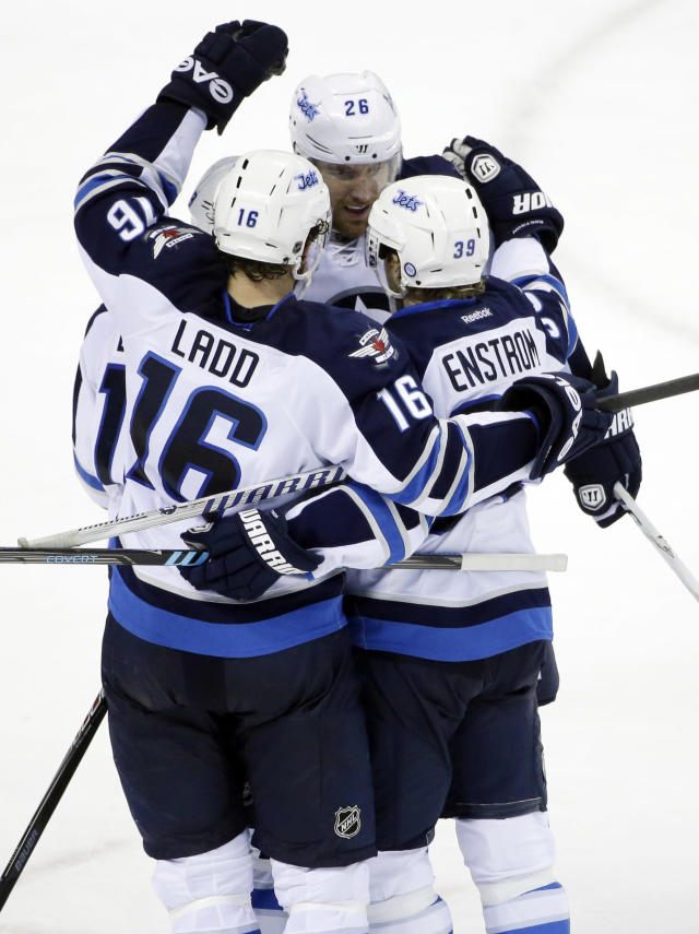 Winnipeg Jets' Tobias Enstrom, bottom right, of Sweden, is hugged by teammates after scoring the go-ahead goal against the San Jose Sharks during the third period of an NHL hockey game on Thursday, March 27, 2014, in San Jose, Calif. Winnipeg won 4-3. (AP Photo/Marcio Jose Sanchez)