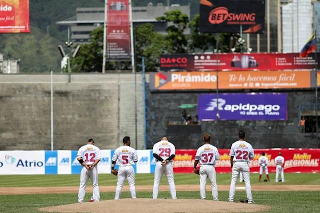 Players of Tiburones de La Guaira team, sing the national anthem before a game at University Stadium in Caracas
