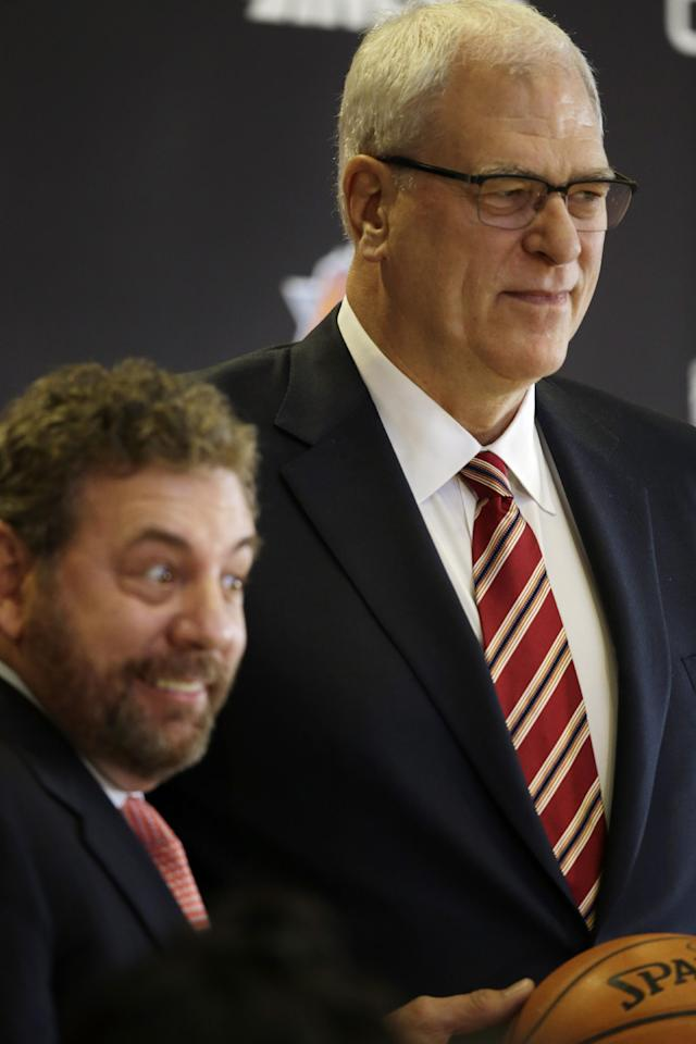 James Dolan, left, executive chairman of Madison Square Garden, smiles as he introduces Phil Jackson as the new president of the New York Knicks, Tuesday, March 18, 2014 in New York. Jackson, who won two NBA titles as a player for the New York Knicks, also won 11 championships while coaching the Chicago Bulls and the Los Angeles Lakers. (AP Photo/Mark Lennihan)