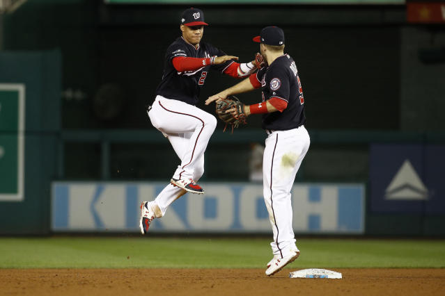 Washington Nationals left fielder Juan Soto, left, and second baseman Brian Dozier (9) celebrate after the final out against the Los Angels Dodgers in Game 4 of a baseball National League Division Series, Monday, Oct. 7, 2019, in Washington. (AP Photo/Patrick Semansky)