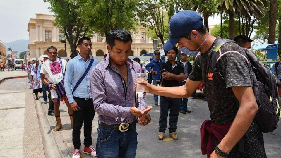 A worker sanitises people`s hands as they queue for an allowance from the local government