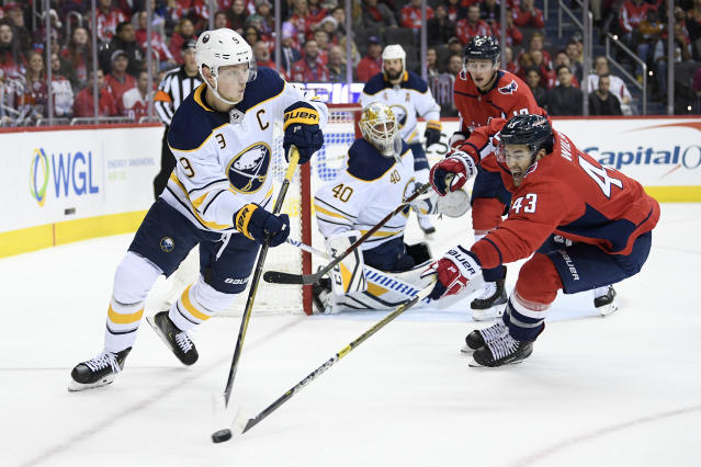 Buffalo Sabres center Jack Eichel (9) skates with the puck against Washington Capitals right wing Tom Wilson (43) during the first period of an NHL hockey game, Friday, Dec. 21, 2018, in Washington. Sabres goaltender Carter Hutton (40) looks on. (AP Photo/Nick Wass)