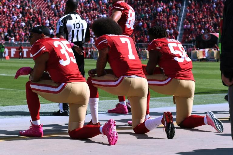 Colin Kaepernick (C), pictured in 2016 with teammates Eric Reid (L) and Eli Harold of the San Francisco 49ers, was one of a number of players who knelt in protest during the national anthem prior to NFL games, drawing the ire of President Trump