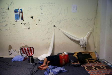 FILE PHOTO: A boy sleeps inside the disused Hellenikon airport where refugees and migrants are temporarily housed in Athens