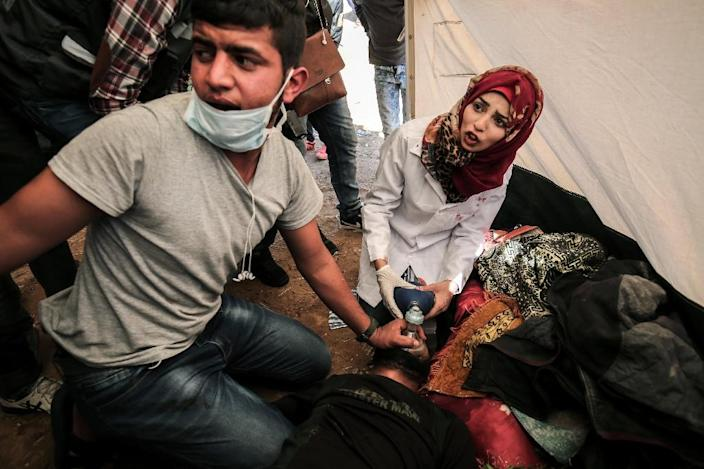 Medical staff help an injured Palestinian man at an emergency medical tent after clashes with Israeli security forces near the border with Israel, east of Khan Yunis, in the southern Gaza Strip, on April 01, 2018 (AFP Photo/SAID KHATIB)