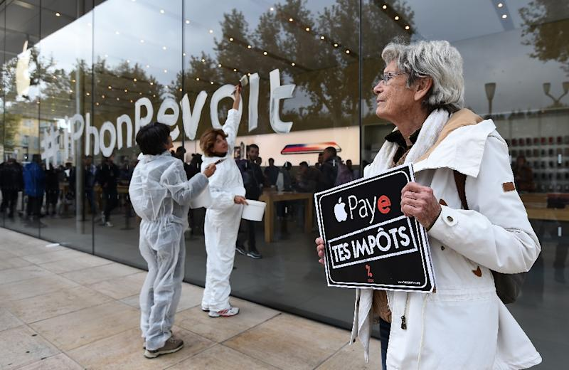 """Protesters in France last week carried signs urging Apple to """"pay your taxes"""" in a reference to its dispute with EU authorities over back taxes (AFP Photo/ANNE-CHRISTINE POUJOULAT)"""