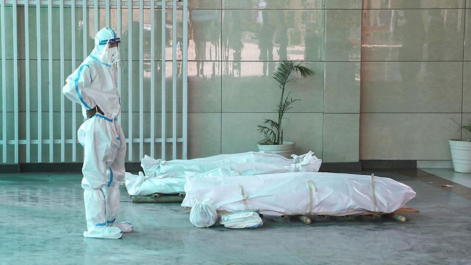 Pictured is a person standing next to the bodies of those who have died of Covid-19 in India