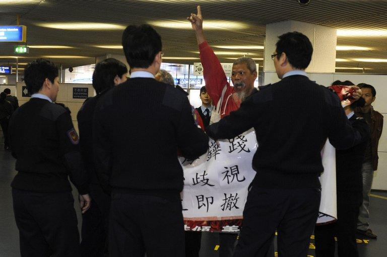 Koo Sze-yiu (C) is escorted by immigration officials after being refused entry into Macau, on March 15, 2009
