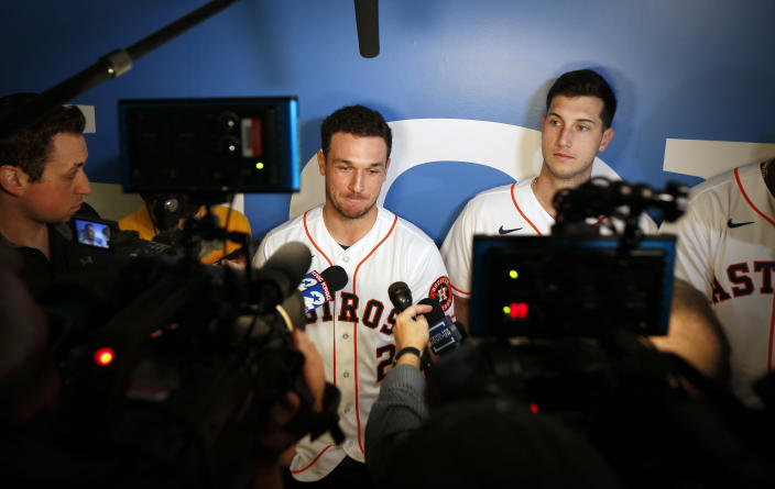 Houston Astros' Alex Bregman, center, is interviewed by the media during the baseball team's FanFest, Saturday, Jan. 18, 2020, in Houston. Astros' Kyle Tucker, right, looks on. (Steve Gonzales/Houston Chronicle via AP)