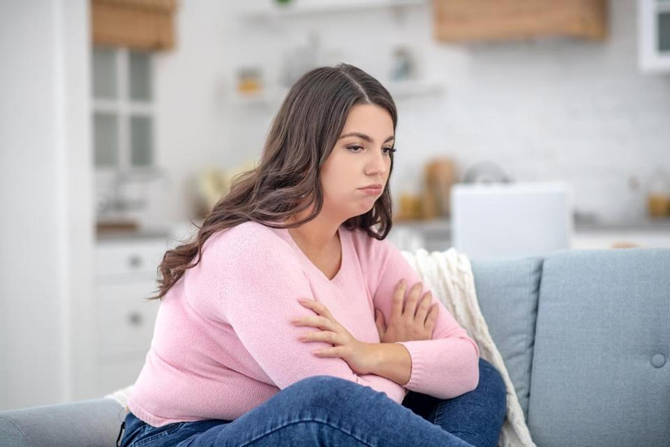 Full-figured young woman in a pink shirt feeling depressed