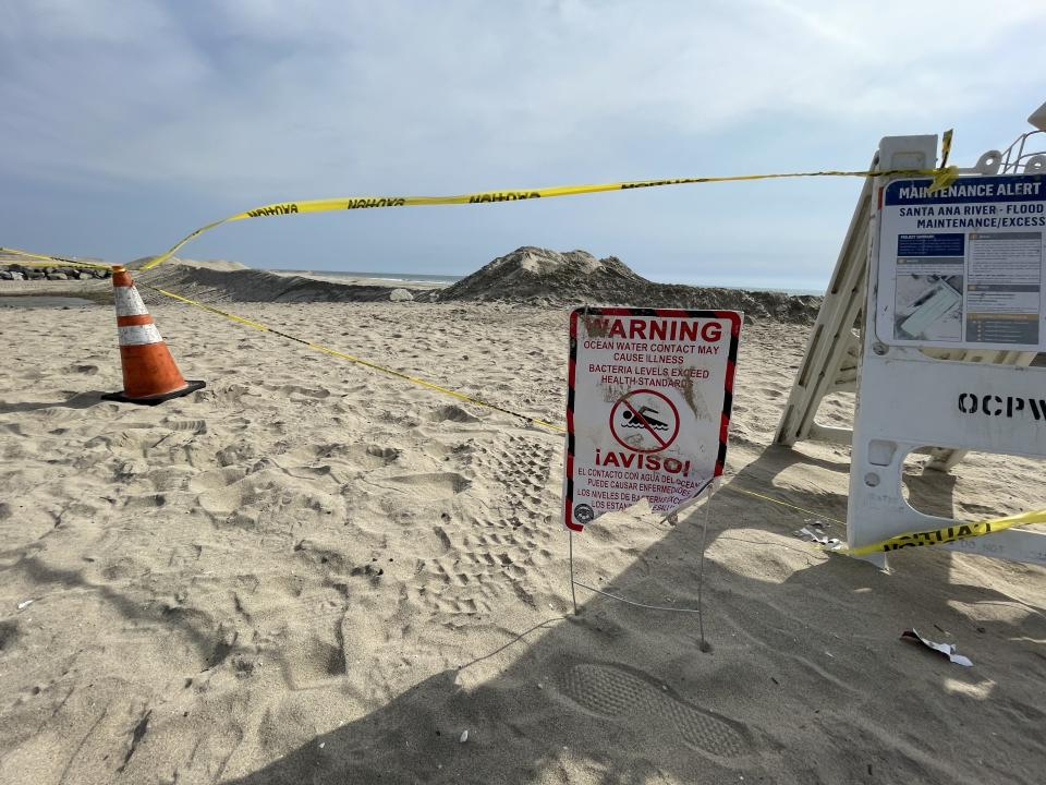 Signs warn beachgoers not to swim following the oil spill that sent 126,000 gallons of crude into the ocean in Orange County, Calif. Caution tape stretches for miles to keep people at bay. (Garin Flowers/Yahoo)