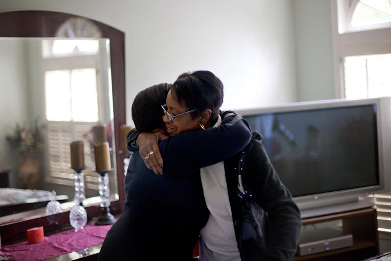 Retired Atlanta police Det. Jaqueline Barber, right, is embraced by former co-worker Robyn Anderson in the home Barber shares with her daughter and four grandchildren Monday, Oct. 8, 2012, in Fayetteville, Ga. Less than a year after Occupy Atlanta members clashed with police in riot gear in a downtown park, they're now protesting alongside officers to help Barber avoid losing her home to foreclosure. Barber said she is under threat of eviction after her medical bills mounted, partly because of a diagnosis of multiple myeloma, a form of blood cell cancer. If she's evicted, she expects that she will be homeless. (AP Photo/David Goldman)