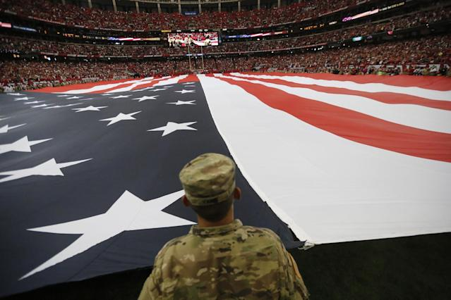 <p>A member of the military holds a giant American flat during the national anthem before the first half of an NFL football game between the Atlanta Falcons and the Tampa Bay Buccaneers, Sunday, Sept. 11, 2016, in Atlanta. (AP Photo/David Goldman) </p>