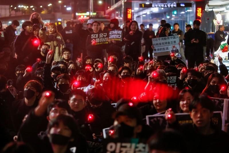 Students and young people point laser pens during a demonstration to support Hong Kong pro-democracy protesters in Seoul