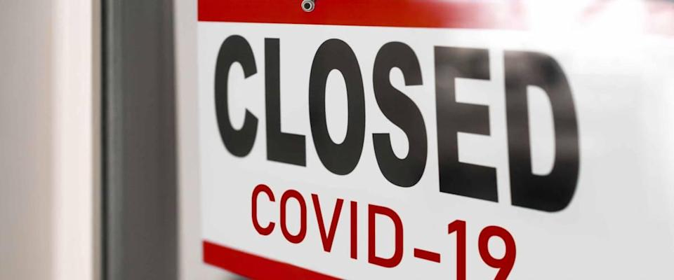 Closed businesses for COVID-19 pandemic outbreak, closure sign on retail store window.