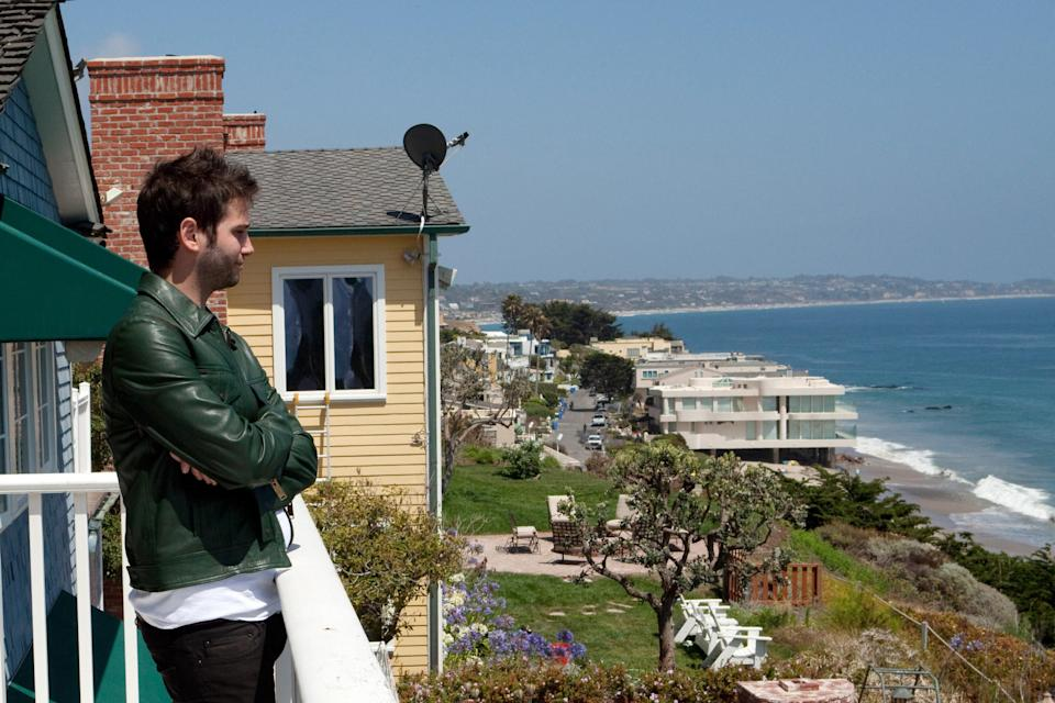 Josh Flagg looks over the ocean from a balcony