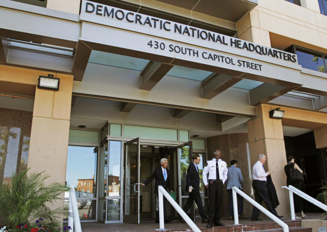 FILE - In this June 14, 2016 file photo, people stand outside the Democratic National Committee headquarters in Washington. Hackers tried to break into DNC inboxes in March 2016 and intensified their efforts in early April. (AP Photo/Paul Holston, File)