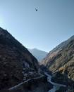 A helicopter conducts an aerial survey after a Himalayan glacier broke and crashed into a dam at Raini Chak Lata village in Chamoli district